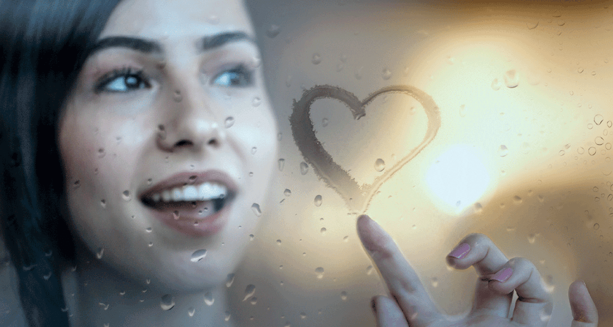 Young lady paints heart in steamed-up window