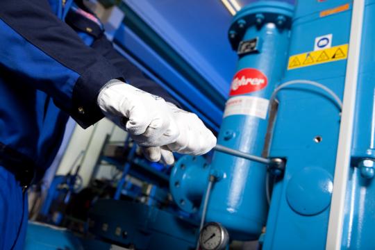 Mehrer El técnico de servicio atornilla la tapa del cilindro del compresor