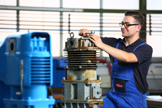 Mehrer Service technician screws on the cylinder cover of the compressor